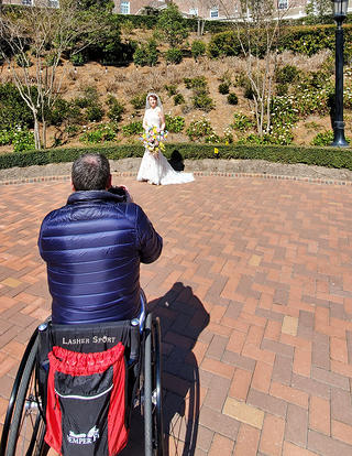 Image of a man in a wheelchair taking a photograph of a woman in a wedding dress on a brick area. In the background, cropped, is some landscaping and a larger brick building with an L shaped layout.