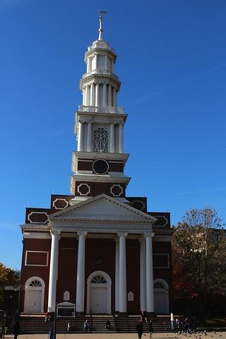Exterior view of a church made up of red brick. There are a series of steps leading to the entrance which has four white columns and a white steeple.