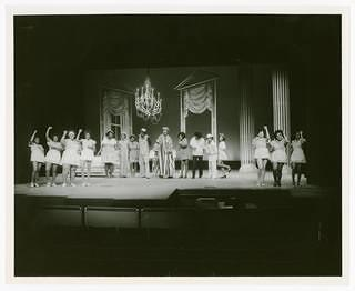 View of a stage at a theatre with some dancers on the right and left and a group of other actors in the center. There is a chandelier hanging from the ceiling with two columns in the rear of the stage.