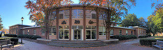 Exterior panoramic view of the Spelman Rockefeller Fine Arts building. The center section has four relief images on the awning style windows. The building is largely made up of red brick.