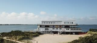 A wide angle view of a beached barge with  three colorful squares on one of the upper stories and a ramp leading up to the entrance. It is white and black with a small beach in front and the expanse of the bay behind it.