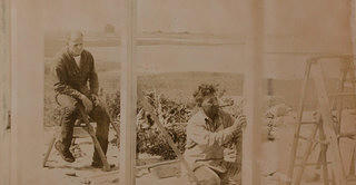 A sepia toned image with a man working on constructing some walls while another man sitting behind him observing with a cigarette in his hand. The background is of a bay of water and an open landscape..
