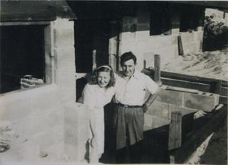 Black and white image of a man and a woman sitting inside a home that is under construction. Mabel is leaning over,  with wide smile across her face, and Victor has a hand on his hip looking forward.