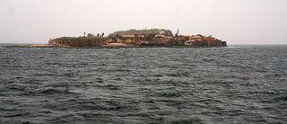 View of  Gorée Island in Senegal with an expanse of water from the Atlantic Ocean in front. The buildings on the island are a coral color while the sky and water are a deep dark blue.