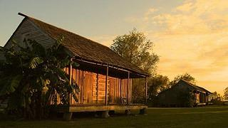 A view of one of the slave cabins, a vernacular structure made of brown boards and a small porch against the backdrop of a sunset.