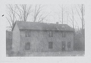 A faint black and white image of A single building with two floors. there are three windows at the top, and the windows and a door at the bottom. The structure is surrounded by bare trees.