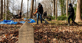 In the foreground is a gravestone in this image while in the background four individuals are performing various cleanup tasks in a wooded area, including raking leaves and collecting debris.