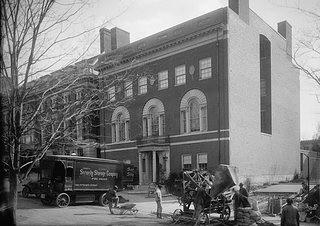 Black and white image of a moving truck in front of a stately three story home in Washington, D.C. The truck says Security Storage Services and there are some workers with what wheelbarrows and equipment standing by.