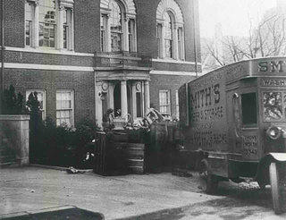 Black and white image of a moving truck in front of a stately three story home in Washington, D.C. Various home furnishings are coming out of the truck.