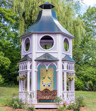 A short lavender building with a metal roof. The structure has a step up into it with an ornate seat that is placed below a yellow painted butterfly, and it has flower boxes hanging from some lattice work above the seating area.. The building sits in a clearing through there is a wooded treeline surround it.