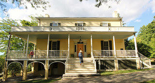 An exterior view of a yellow house with a full length portico. A walkway and approximately 10 steps lead to the front door. The house sits on a rise so on the left side of the pictures are three archways leading to a lower area.