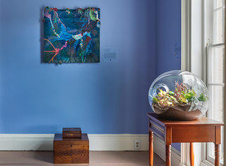 The interior of a blue painted room. On the far wall is a deep blue painting with beadwork with a two wooden stacked boxes sitting below it. To the right is a window with a wooden table in the foreground. On the table is a round glass terrarium (a globe like structure with a opening) with various plants within it.