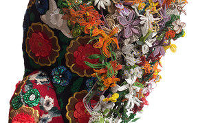A close up of some of the details on Nick Cave's Soundsuit. In this image viewers can see a combination of material including knitwear, sequences, and beaded material in the form of flowers.