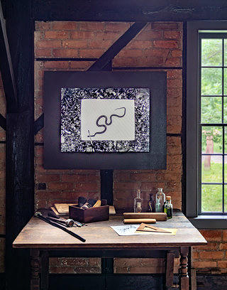 A framed black and white image with pattern and a snake sits above an artist desk against a brick wall, with various tools such as brushes, paper, rulers etc. On the right hand side is a window.