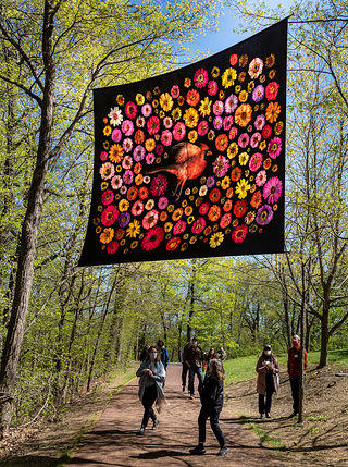 A photograph of a silk screen spread out across a tree lined path with people walking underneath. The screen has a cardinal bird in the middle with florals in pink, yellow, purples, and reds surrounding the bird.