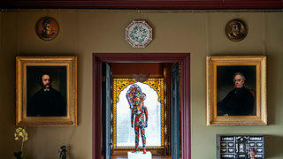 A wide view of Nick Cave's Soundsuit within Olana. We are looking at the brightly crafted human shaped suit through a series of doors in the space. From the vantage point the suit is framed within a stained glass with yellow detail and flanked by two formal portraits of men.