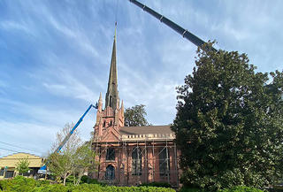 Long view of the Trinity Abbeville church with a crane overhead as they stabilize the Spire. There are a set of trees covering the back of the church and a lower frame house on the far left of the image. A smaller crane that is blue sits in front of building.