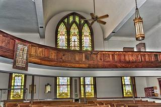 Interior view of the First Congregational United Church of Christ. Wooden pews in two levels in a curved shape are in front of a series of stained glass windows. There is a fan and a lantern hanging down from the ceiling.
