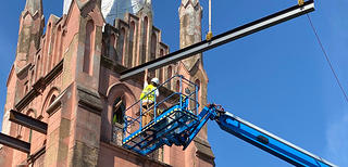A detail view of the steeple of brown stone church where a crane is putting in steel beams for stabilization. There are two construction workers, one on the crane and one in the steeple guiding the beam in.