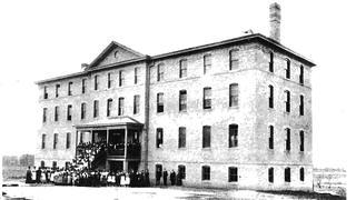 A black and white image of building at Jackson State. It is brick and has four floors. This image has a group of people standing on the stairs leading up to the entryway and across the front. There are no other buildings around it.