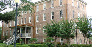 Exterior view of a brick building with a portico entryway with a series of stairs leading up to front door. The building is four floors with twelve windows visible across the third floor. A tree obscures part of the top floor.